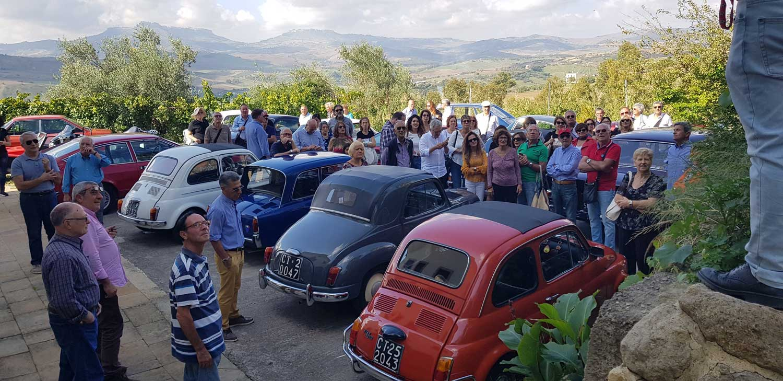 Un gruppo di persone è all'esterno dell'azienda Samperi in occasione di un raduno a Leonforte.