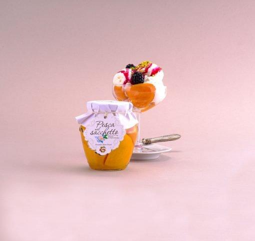 Una gustosissima coppa di gelato alla vaniglia viene arricchito dalle pesche nel sacchetto di Sampieri, more, sciroppo di fragola e scaglie di pistacchio