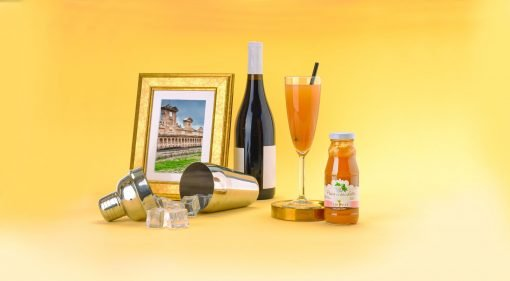 Una composizione solare con shaker per cocktail, una bottiglia di prosecco e succo di pesca per creare il famoso drink Bellini.